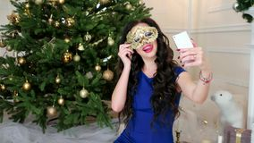 Maakt het Mooie meisje van de Kerstmismaskerade in gouden masker selfie mobiele telefoonselfifoto tijdens de viering van Nieuw stock footage