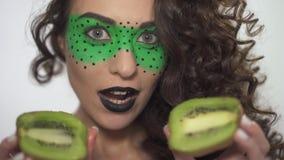 Maakt het portret mooie smilling krullende meisje met helder omhoog het houden van de twee helften van kiwi stock footage