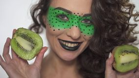 Maakt het portret vrij smilling krullende meisje met helder omhoog het houden van de twee helften van kiwi stock videobeelden