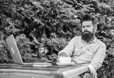 Maakt mensen gebaarde hipster pauze voor drinkt koffie en denkt terwijl met laptop zit De kerel drinkt koffie het ontspannen terr stock afbeelding