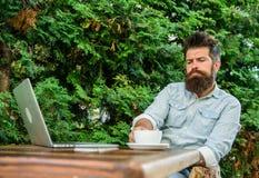 Maakt mensen gebaarde hipster pauze voor drinkt koffie en denkt terwijl met laptop zit De kerel drinkt koffie het ontspannen terr royalty-vrije stock foto