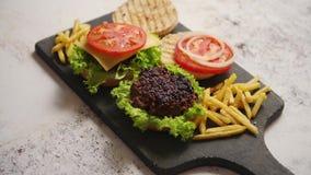 Maakte smakelijk geroosterd huis twee burgers met rundvlees, tomaat, ui en sla stock footage