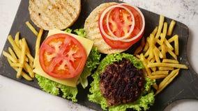 Maakte smakelijk geroosterd huis twee burgers met rundvlees, tomaat, ui en sla stock videobeelden