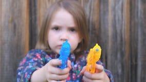 Maakte weinig vaag meisje bang houdt in handen een oranje en blauw stuk speelgoed kanon stock video