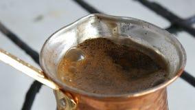 Maalde zwarte koffie in een koper Turk wordt gebrouwen en kookt op een gasfornuis Barista die hete smakelijke drank thuis dicht v stock footage
