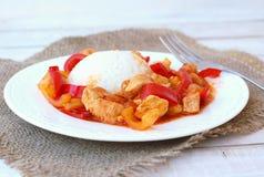 Maaltijd van kippenvlees met Indische kruiden, groene en Spaanse peper en rijst op witte plaat, jutedoek en hout met vork Royalty-vrije Stock Afbeelding