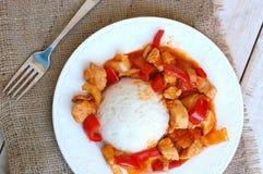 Maaltijd van kippenvlees met Indische kruiden, groene en Spaanse peper en rijst op witte plaat, jutedoek en hout met vork Stock Afbeeldingen