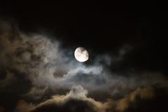 Maan die door donkere wolken bij nacht wordt omringd royalty-vrije stock foto's