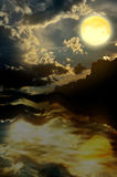 Maan met nightly wolken over het water stock afbeelding
