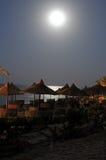Maan over strandparaplu's stock afbeelding