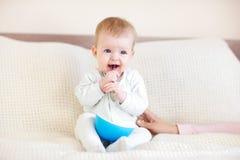 8 maandbaby die van de kom eten Stock Foto's