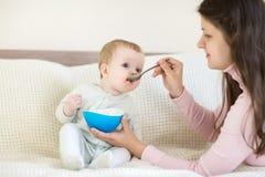 8 maandbaby die van de kom eten Stock Afbeeldingen