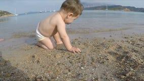 10 maanden baby het spelen met zand op het strand stock footage