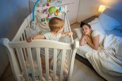 9 maanden oud baby die zich in voederbak en ontwaken vermoeid zijn bevinden mothe royalty-vrije stock afbeeldingen