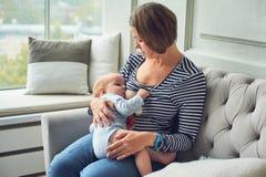8 maanden oud baby diemoeder` s melk eten De babyjongen van de moeder de borst gevende zuigeling, die op bank thuis binnenland si royalty-vrije stock foto's