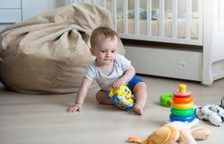9 maanden oud babyjongen het spelen met stuk speelgoed auto en stuk speelgoed toren Royalty-vrije Stock Afbeelding