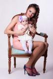 6 maanden van het babymeisje de zittings op de overlapping van de moeder en het levensonderhoud hallo Royalty-vrije Stock Afbeelding