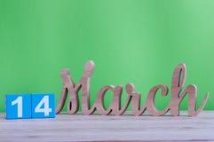 14 maart Dag 14 van maand, dagelijkse houten kalender op lijst en groene achtergrond De de lentetijd… nam bladeren, natuurlijke a Stock Foto's