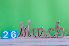 26 maart Dag 26 van maand, dagelijkse houten kalender op lijst en groene achtergrond De lentetijd, lege ruimte voor tekst Stock Fotografie