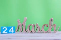24 maart Dag 24 van maand, dagelijkse houten kalender op lijst en groene achtergrond De lentetijd, lege ruimte voor tekst Stock Foto's