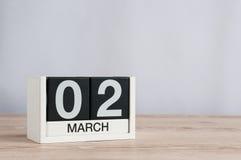 2 maart Dag 2 van maand, houten kalender op lichte achtergrond De lentetijd, lege ruimte voor tekst Stock Afbeelding