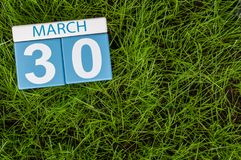 30 maart Dag 30 van maand, kalender op achtergrond van het voetbal de groene gras De lentetijd, lege ruimte voor tekst Stock Afbeelding