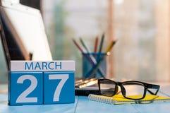 27 maart Dag 27 van maand, kalender op bedrijfsbureauachtergrond, werkplaats met laptop en glazen De de lentetijd… nam bladeren,  Royalty-vrije Stock Afbeelding