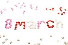 8 maart, de dag van wereldvrouwen ` s, wordt geschreven op een witte achtergrond met kleine suikerharten isoleer Stock Afbeeldingen