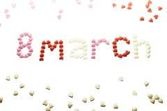 8 maart, de dag van wereldvrouwen ` s, wordt geschreven op een witte achtergrond met kleine suikerharten isoleer Royalty-vrije Stock Foto