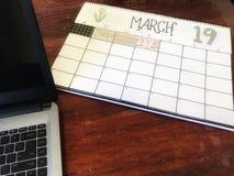 19 maart kalender op bureau met laptop computer stock afbeelding