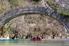 27 maart 2011 Konitsa, Griekenland - Rafting in Voidomatis-rivier, Epirus, Griekenland, onder een oude steenbrug Royalty-vrije Stock Afbeeldingen