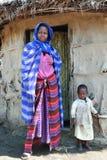 Maasai妇女,当孩子站立在他的小屋的门 免版税库存图片