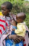 Maasai有一个小婴孩的部落妇女在手上 免版税库存照片