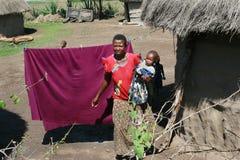 Maasai村庄,深色皮肤的妇女抱一个孩子 免版税库存图片