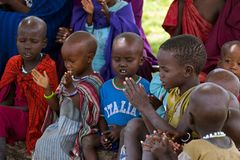 Maasai African kids singing a song under Acacia tree as outdoor school in Tanzania, East Africa. TANZANIA, EAST AFRICA - APRIL 2018 : Maasai African kids singing stock photo
