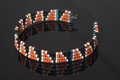 Maasai bracelet. Maasai tribal bracelet with black, orange and white beads over black stock photos
