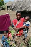 Maasai by, den afrikanska familjen som står nära kojor Arkivbilder