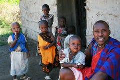 Maasai familj i dörröppningen av hans hem, fader och barn Arkivfoton