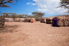 Maasai folk i deras by i Tanzania, Afrika Arkivfoton
