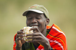 Maasai Guide. A maasai guide dressed in traditional clothes eating a toast Stock Photos