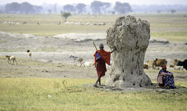 Maasai Herdsmen and Termite Mound Stock Image