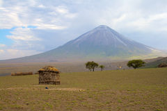 Maasai house with volcano on background Royalty Free Stock Image