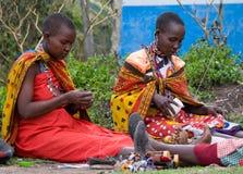 Maasai women. MAASAI MARA, KENYA-DECEMBER 27: Maasai women make traditional necklace 27 December, 2012 at Maasai Mara, Kenya. The Maasai are the most famous Royalty Free Stock Photo