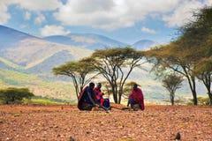 Maasai men sitting. Savannah landscape in Tanzania, Africa. Ngorongoro Conservation Area, TANZANIA, AFRICA - DECEMBER 11: Three Maasai men in traditional clothes stock photography