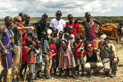 Maasai receiving group of tourists. At the entrance to their village in Kenya on a sunny day is a picture taken in May 2014 Royalty Free Stock Images