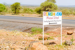 Maasai school sign at the road in Tanzania. Arusha, Tanzania - March 14, 2015: Sign at the road from Arusha to Babati. Sign is pointing direction to Maasai stock images