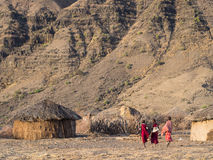 Maasai village in Arusha. Three kids walking in a Maasai village in front of the Ol Doinyo Lengai in Arusha Region in Tanzania, Africa, at sunrise royalty free stock images