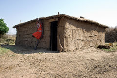 Maasai warrior leaning against his mud build hut. Royalty Free Stock Photos