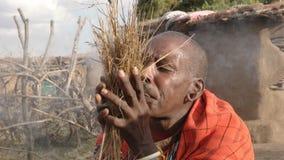 A maasai warrior starts fire the traditional way at a Manyatta in Kenya. A maasai warrior starts a fire the traditional way without matches at a Manyatta in stock video footage