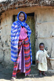 Maasai woman, with child standing at door of his hut. Royalty Free Stock Images